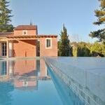 maison construite avec des matériaux moderne et une piscine et pool house
