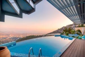 piscine avec vue sur la mer et un eclairage de piscine au coucheé de soleil
